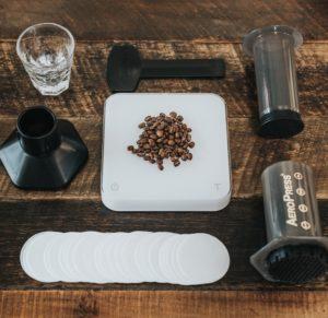 Aeropress kit som är isärplockad med kaffebönor och kaffevåg