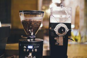 En svart kaffekvarn med kaffebönor och en utan